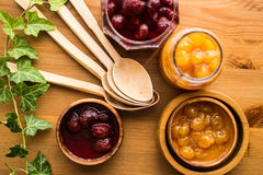 Strawberry and Yellow Cherry Jam on a wooden surface. Royalty Free Stock Image