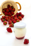 Strawberry yoghurt in a glass jar and basket of strawberries. Stock Images