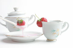 Strawberry yogurt. Dessert. Yogurt, strawberry and cup of tea on white background Stock Photos