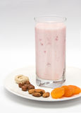 Strawberry yogurt. Glass of strawberry yogurt served with nuts and dried apricots Royalty Free Stock Images