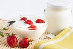 Strawberry yogurt in a bowl and the pot Stock Image