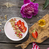 Strawberry yogurt with granola, sliced berries on a wooden background in a white ceramic bowl. Top view.  Stock Photography
