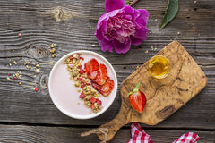 Strawberry yogurt with granola, sliced berries on a wooden background in a white ceramic bowl. Top view.  Royalty Free Stock Image