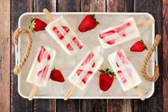 Strawberry yogurt popsicles in a vintage tray against wood. Strawberry yogurt popsicles in a vintage tray against a rustic wooden background Royalty Free Stock Image