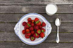 Strawberrys. Bowl with strawberrys and glass of milk on old wood table Stock Photos