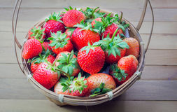 Strawberrys-Beeren in einem Korb auf dem Bretterboden Stockbild