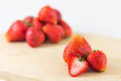 Strawberrys på trä på vit bakgrund Arkivfoton