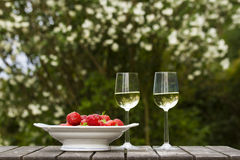 Strawberrys and white wine. On old wood table Stock Image