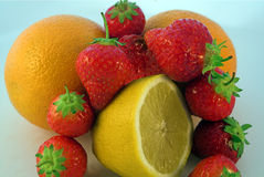 Straws & Citrus. Strawberries encircling oranges with a half-lemon Royalty Free Stock Images