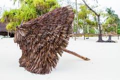 Straws umbrella on white Zanzibar beach. Landscape with thatch tiki umbrella on the white beaches of the Indian Ocean spice island of Zanzibar Unguja, Tanzania Stock Image