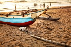 Stray dog laying on the beach sand, in front of fishing boat stock image