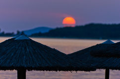 Stray sunshades at beach with orange sunset in background, Sithonia. Greece Royalty Free Stock Photos