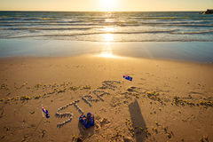 Straya text, flag and thongs on beach. Straya text drawn using shells on sand with flags and thongs. Straya is an abbreviation of Australia Royalty Free Stock Photos