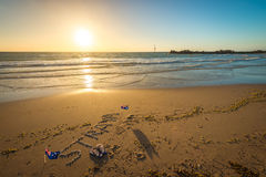 Straya text, flag and thongs on beach. Straya text drawn using shells on sand with flags and thongs. Straya is an abbreviation of Australia Royalty Free Stock Photo