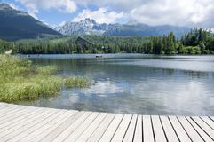 Strbske pleso, High Tatras mountains, Slovakia, early summer morning, lake reflections, wooden pier Royalty Free Stock Photos