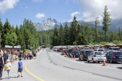 Strbske pleso, High Tatras / Slovakia - July 9, 2017: Footpath and road to the mountains with cars and people, beautiful day royalty free stock images