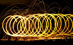 Spiraling long exposure fire. Streaks of fire from steel wool on fire during a long exposure night shot Royalty Free Stock Photography