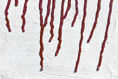 Streaks of red paint on the whitewashed wall. In the background Stock Photography