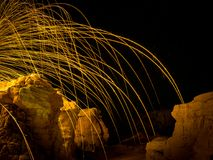 Steel wool arcs over cliffs. Streaks and sparks from burning steel wool arching over illuminated rock formation at night Stock Image