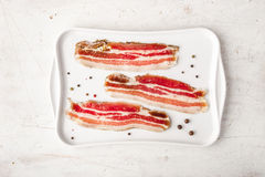 Streaky bacon with black pepper on the white plate top view Royalty Free Stock Photo