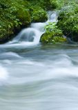 Stream. A stream or creek, is a body of water with a detectable current, confined within a bed and banks Stock Images
