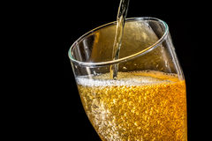 Stream of beer being pouring into a glass with beer and foam isolated on black background, closeup texture Stock Image