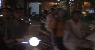 Stream of bikes and cars in night Hanoi, Vietnam. HANOI, VIETNAM - OCTOBER 27, 2015: Road traffic in night city. Motorbikes stream and several cars moving along stock video