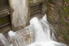 Stream blurred water in small waterfall in dam Royalty Free Stock Photos