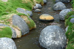 A stream with boulders and moss Stock Photos