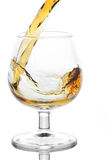 Stream of brandy falling in glass. On a white background Stock Photography