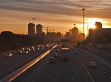 Stream of cars traveling on a busy highway. The beginning of morning rush hour, cars on the highway traveling to and from  downtown Royalty Free Stock Image