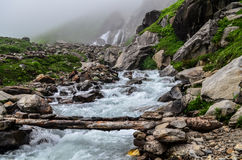 Stream at Chika - Hampta pass trek. A view of stream at Chika campsite with waterfall in background Royalty Free Stock Images