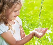 Stream of clean water pouring into children's hands Royalty Free Stock Photo