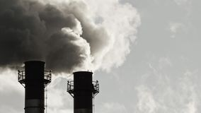 Stream of dark smoke from the chimney of factory. In the industrial district stock footage