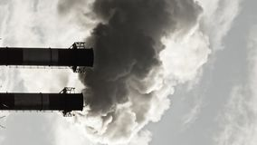 Stream of dark smoke from the chimney of factory. Vertical shot of stream of dark smoke from the chimney of factory in the industrial district stock video footage
