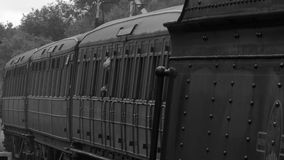 B&W shot of steam engine coming into station 4K. Stream engine pulling carriages black and white image 4K stock footage