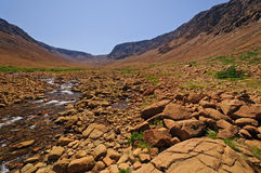 Stream flowing through arid hills Stock Photo