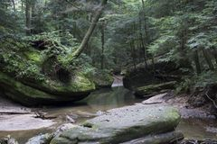Stream flowing by boulders. A slow moving creek flows past large boulders in Hocking Hills State Forest at the Old Man`s Cave area near Logan, Ohio stock images