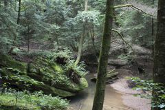 Stream flowing by boulders. A slow moving creek flows past large boulders in Hocking Hills State Forest at the Old Man`s Cave area near Logan, Ohio royalty free stock photo