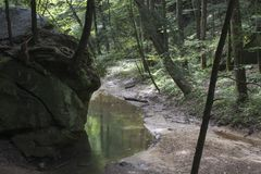 Stream flowing by boulders. A slow moving creek flows past large boulders in Hocking Hills State Forest at the Old Man`s Cave area near Logan, Ohio stock photo