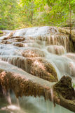 A stream flowing through foggy Autumn woodland at Erawan falls in Thailand National park Royalty Free Stock Image