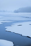 Stream flowing through frozen lake Stock Images