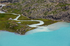 Stream flowing from glacier to Ala-Kul lake Stock Photos