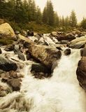 Stream flowing in motion over rocks. Stock Photos