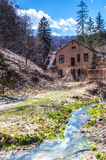 Stream flowing next to a house. Stream flowing next to a deserted house Royalty Free Stock Photos
