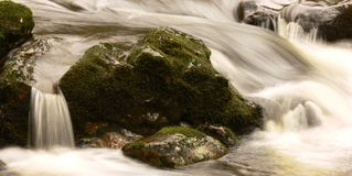 Stream flowing over rocks. Stream flowing over mossy rocks using long exposure Stock Images