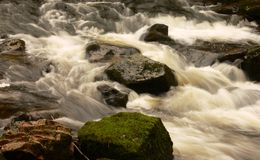 Stream flowing over rocks. Scenic view of stream flowering over moss covered rocks with slow motion blur Stock Photography