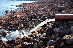 Stream flowing from a pipe on rocks in spring Royalty Free Stock Photos