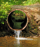 Stream Flowing into River. This midday shot was taken of creek water running through a drain pipe into a river royalty free stock image