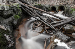 Stream flowing between rocks and branches Royalty Free Stock Images
